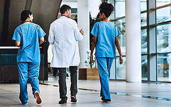 Doctor talking to nurses while walking